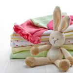 Pile of colorful baby clothes nad toy on white wooden background